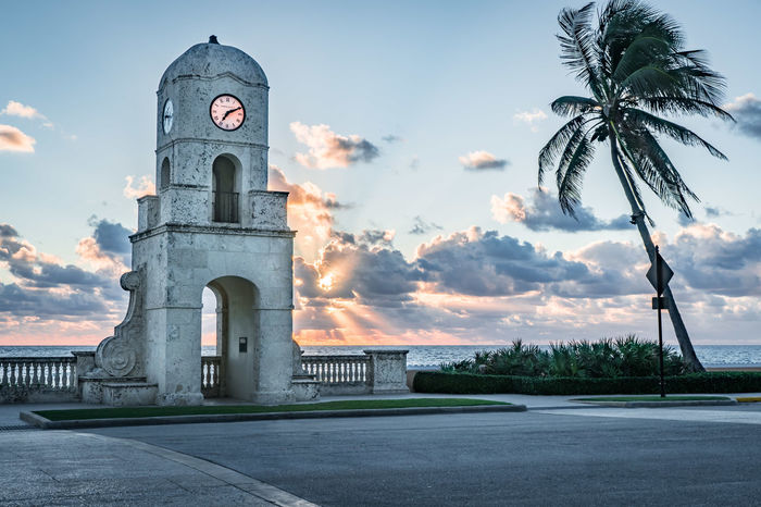 Clock Tower at end of Worth Avenue, Town of Palm Beach, Florida Ocean View Worth Ave, Palm Beach, F Worth Avenune Architecture Beach Building Exterior Built Structure Clock Tower Cloud - Sky Coconut Palm Tree Day History Nature No People Ocean Outdoors Road Sky Sunrise Sunset Travel Destinations Tree