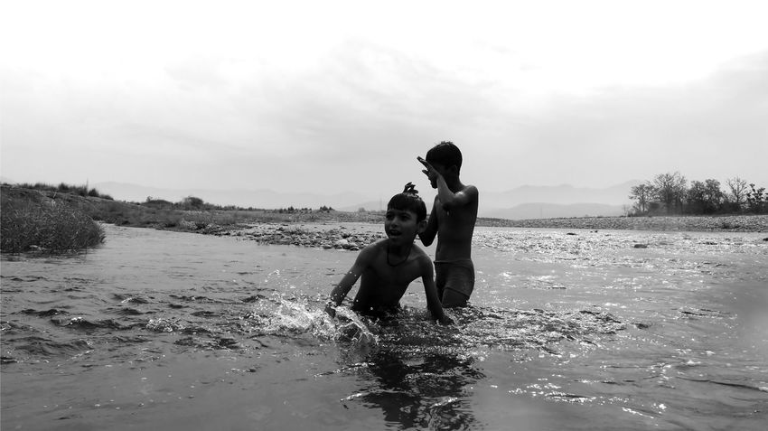 boys having fun in ganges Bonding Boys Childhood Day Fun Funinwater Ganges Ghat Leisure Activity Love Nature Outdoors Portrait River Shirtless Sky Splashing Togetherness Water
