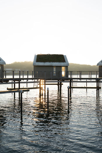 Stilt houses over lake against clear sky
