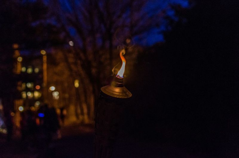 Close-up of lit tiki torch at night