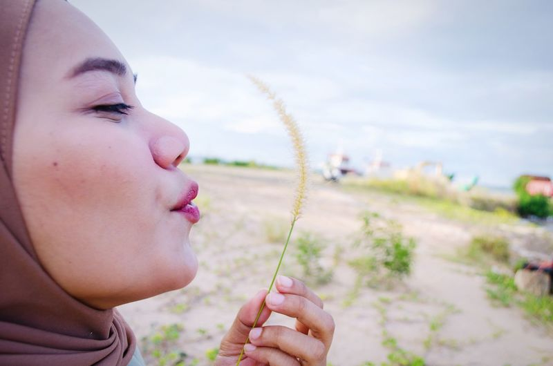 Beautiful hijab woman blowing grass