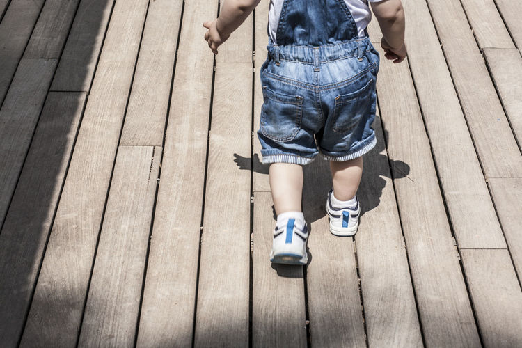 Low section of boy walking on deck