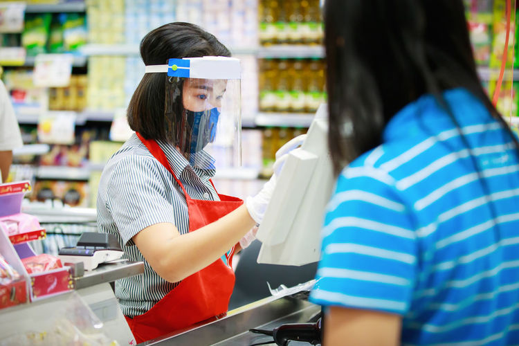 Cashier or supermarket staff in medical protective mask and face shield working at supermarket.