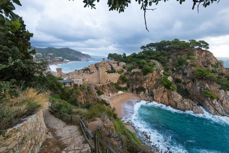Beach and the fortress of Tossa de Mar, Spain, against cloudy sky Water Sea Sky Tree Cloud - Sky Land Nature Beach Scenics - Nature Beauty In Nature No People Coastline Wave Aquatic Sport Outdoors SPAIN Tossa De Mar Fortress Castle Hiking Vacations