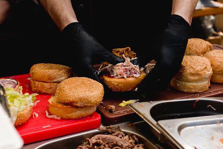 Midsection Of Vendor Preparing Hamburgers On Table At Market