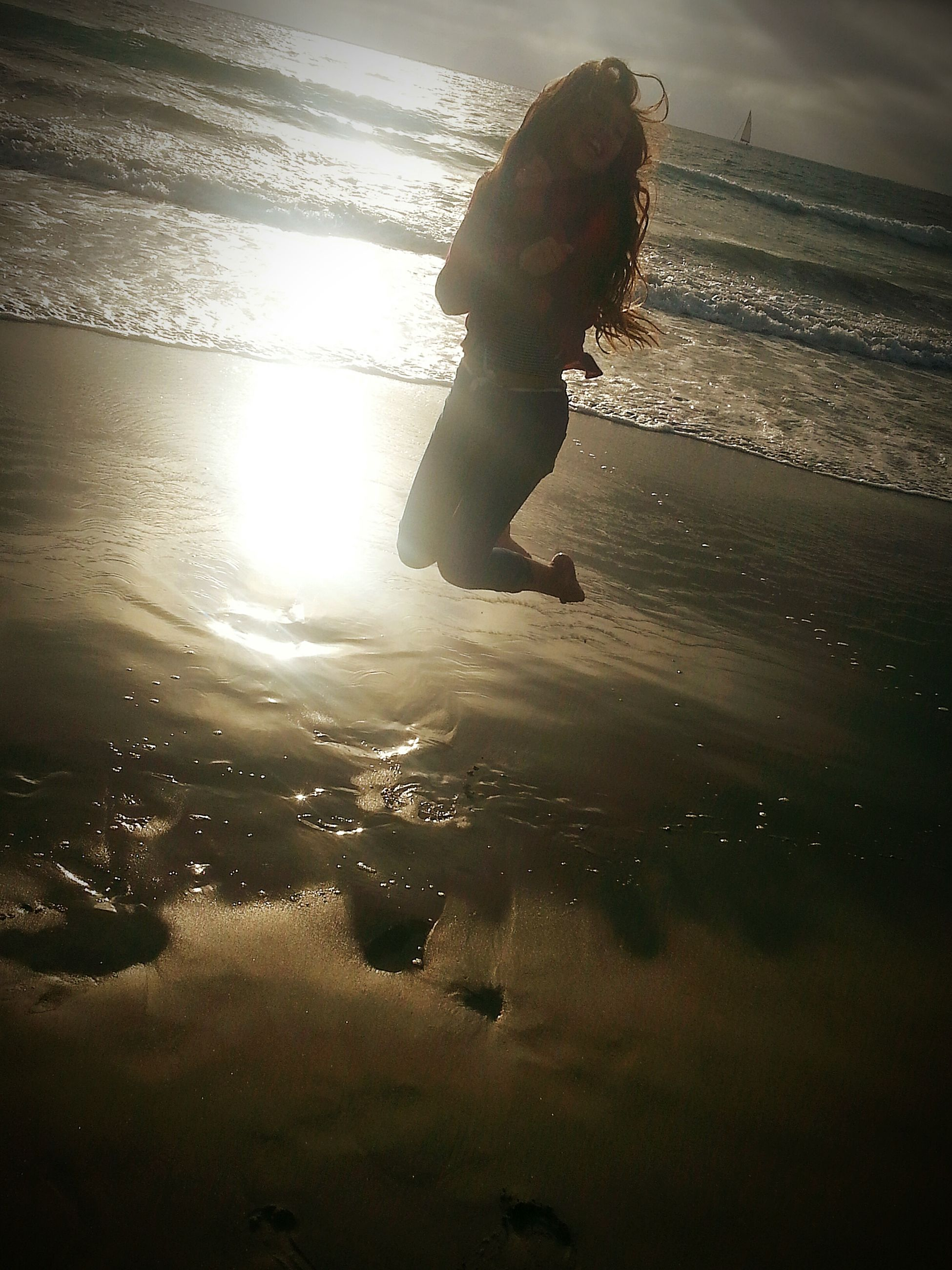 water, beach, shore, sea, sand, reflection, tranquility, sunlight, sunset, sun, nature, sky, leisure activity, silhouette, full length, tranquil scene, beauty in nature, lifestyles
