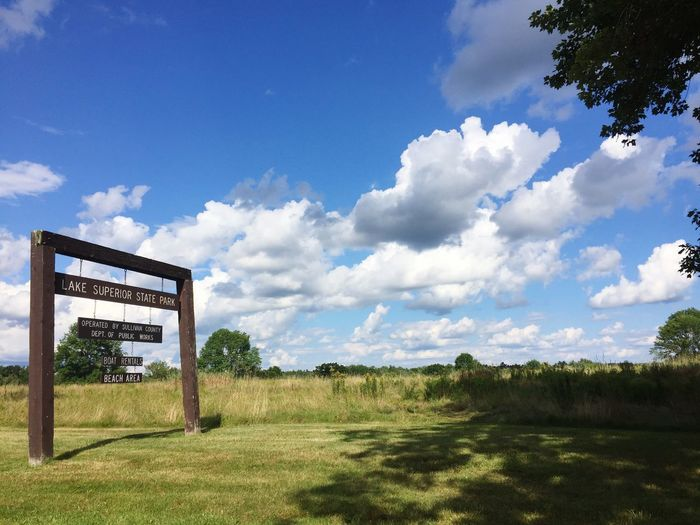 Sign board at lake superior state park against cloudy sky