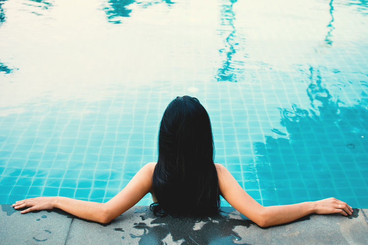 Rear View Of Woman Leaning At Poolside