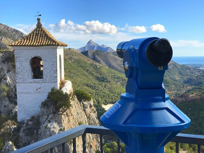 Binoculars and bell tower against sky