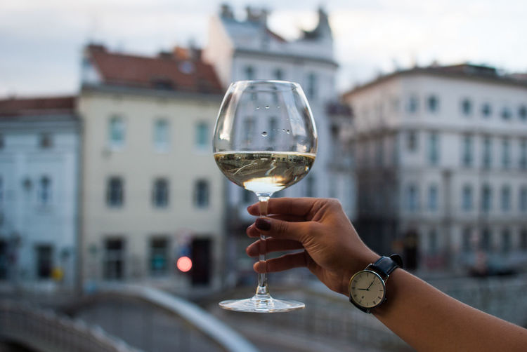 Cheers! Alcohol Architecture Building Exterior Built Structure City Close-up Day Drink Enjoying Life Focus On Foreground Food And Drink Holding Human Body Part Human Hand Lifestyles One Person Outdoors People Real People Refreshment Sky Wine Wine Not Wineglass Woman