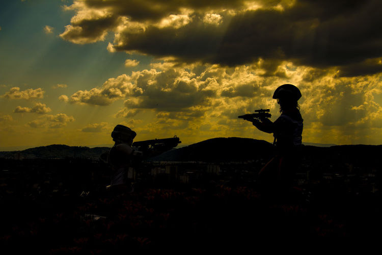 Silhouette people paintballing against cloudy sky during sunset
