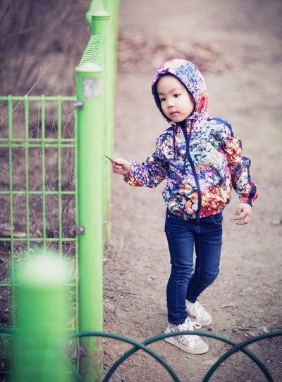 Girl wearing hooded sweatshirt walking by green metallic fence