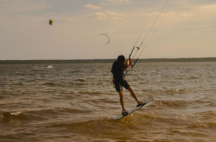 Kitesurfen at the Bärwalder Lake Kitesurfen Adventure Beach Beauty In Nature Day Extreme Sports Full Length Holding Horizon Over Water Kiteboarding Leisure Activity Lifestyles Men Mid-air Nature One Person Outdoors Real People Sea Skill  Sky Sport Standing Sunset Water
