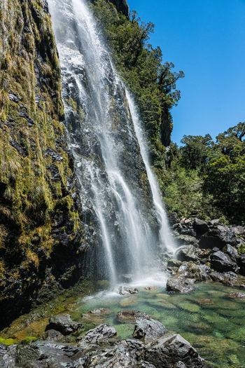 Low angle view of waterfall on rocks
