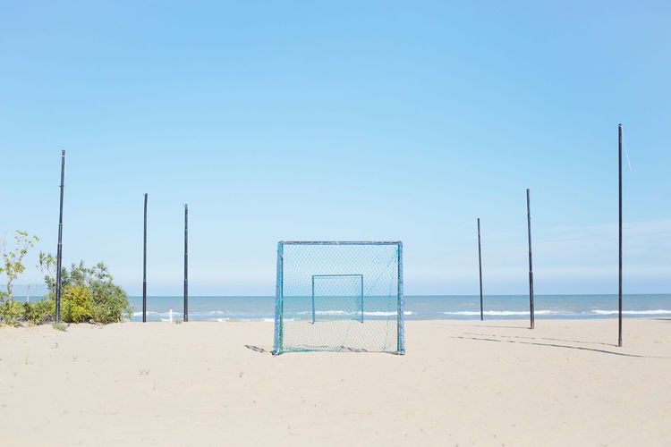 Soccer goal on sand against clear sky at beach