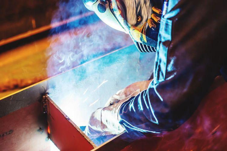 Side view of worker welding metal