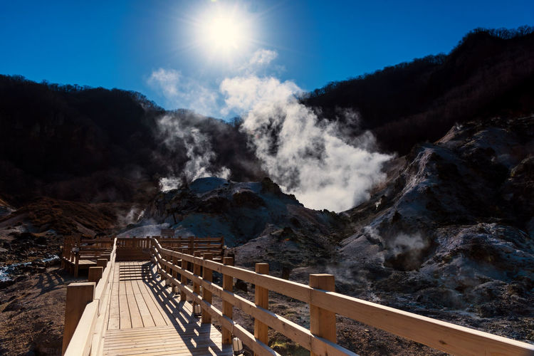 Jigokudani hell valley walking trail or wood footpath with sulfur misty, blue sky, and sunbeam