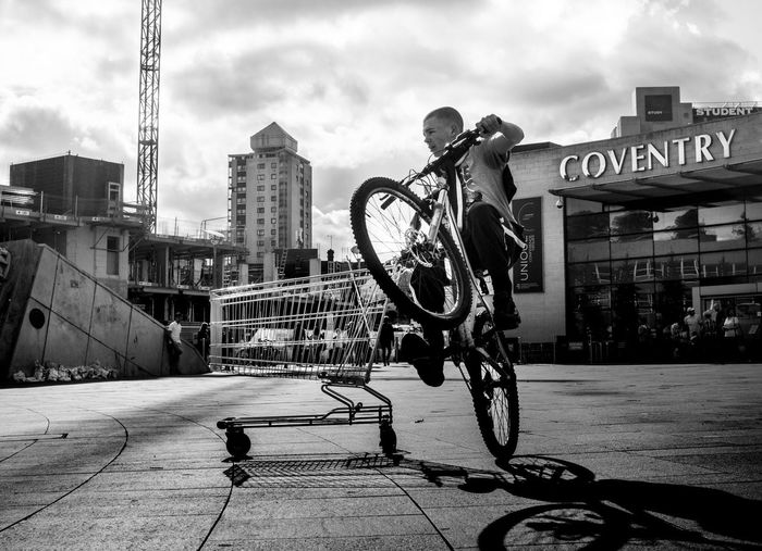 Coventry Streetphotography Blackandwhite Photography Cityscapes City Architecture Building Exterior Built Structure Bicycle Transportation Mode Of Transport City Life Sky Cloud - Sky Outdoors Day Creativity Tall - High Young Adult Shopping Trolley Wheelie Plaza