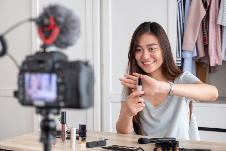 Smiling woman blogging while holding lipstick on table