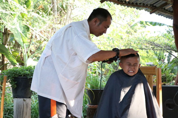 Mature barber trimming scared boy hair at shop against trees