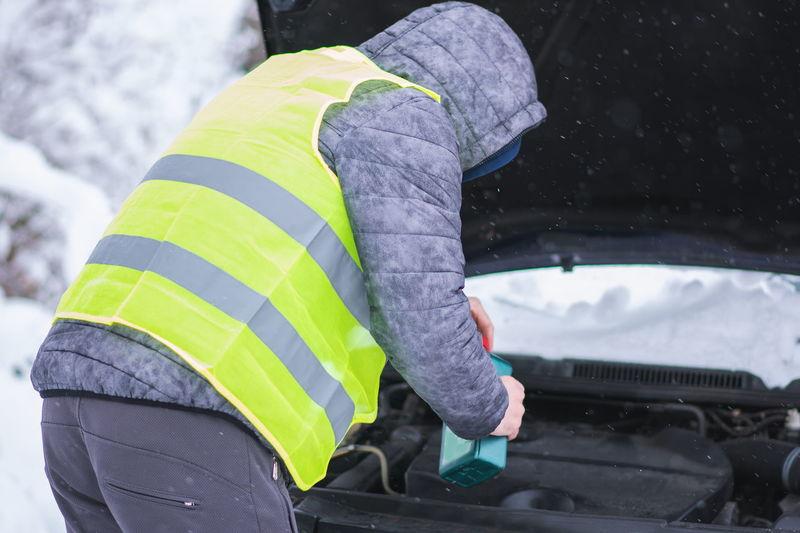 Rear view of man repairing car