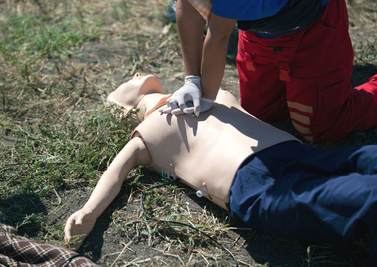 Midsection of woman examining cpr dummy on field