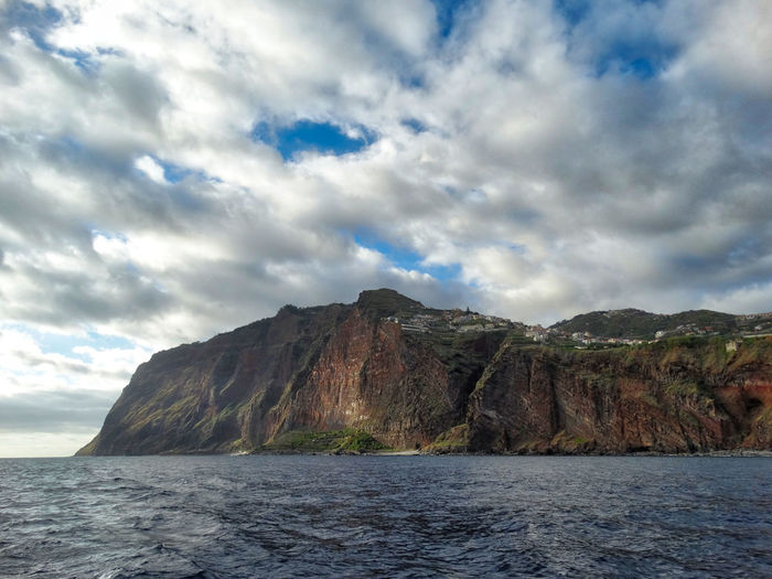 A scene of Madeira Island. Sky Cloud - Sky Beauty In Nature Scenics - Nature Water Mountain Tranquil Scene Tranquility No People Nature Waterfront Rock Sea Day Rock - Object Mountain Range Solid Non-urban Scene Land Outdoors Formation Madeira Island