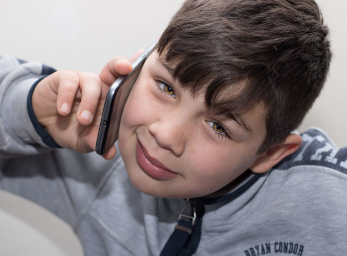 Portrait of boy talking on mobile phone at home