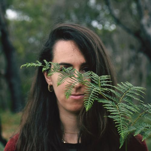 Close-up portrait of young woman against plants