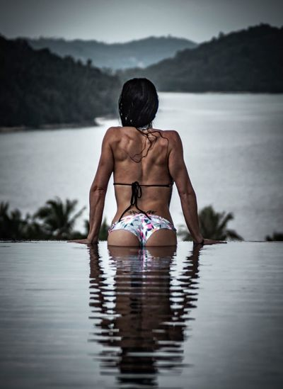 Rear view of muscular woman wearing bikini in infinity pool against lake