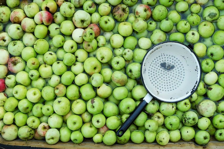 High angle view of green apples with basket in water