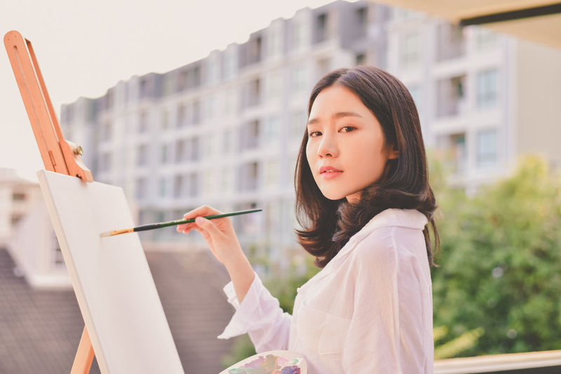 Portrait of woman painting on canvas at home