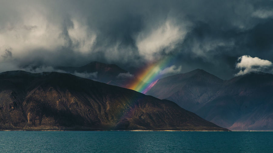 Rainbow over lake and mountains against sky