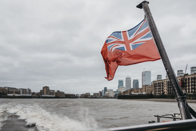 British flag waving on boat in river against sky