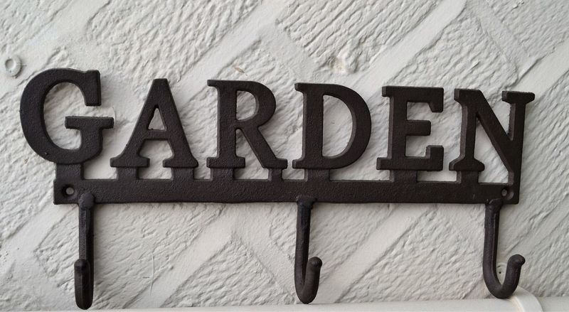 Metal Garden sign with hooks or hangers against a painted brick wall Close-up Garden Hanger Hook Metal Sign No People Signage Single Word Text Wood - Material