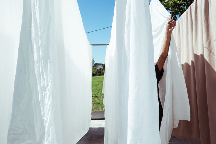 Close-up of clothes hanging on clothesline against sky