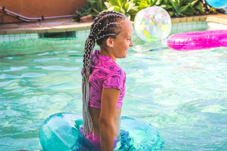 young girl having fun in the pool with an inflatable ring Childhood Child Water Pool Swimming Pool One Person Girls Real People Leisure Activity Women Females Three Quarter Length Lifestyles Day Innocence Nature Swimming Swimwear Outdoors Inflatable  Hairstyle Vacations Summer Long Hair