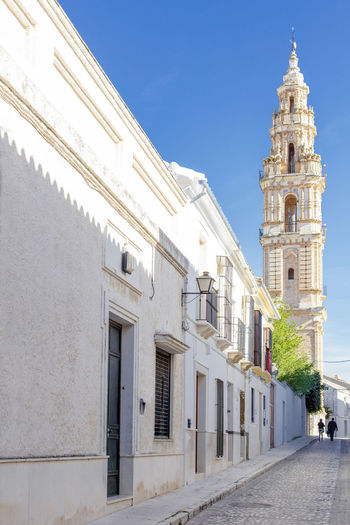 Beautiful Street in Estepa (province of Seville) with Tower of Victory in the background. Charming white village in Andalusia. Southern Spain. Picturesque travel destination on Spain. Estepa Sevilla Estepa SPAIN Seville Tourism White Villages Sun Sky Europe Cityscape Andalusia Andalusian Architecture City Town Village Andalucía Travel Travel Destinations Blue Architecture Tower Summer Outdoors European  Tourist Mediterranean  Traveler Beautiful Province Street Spanish Traditional Destination Vacations Landmark