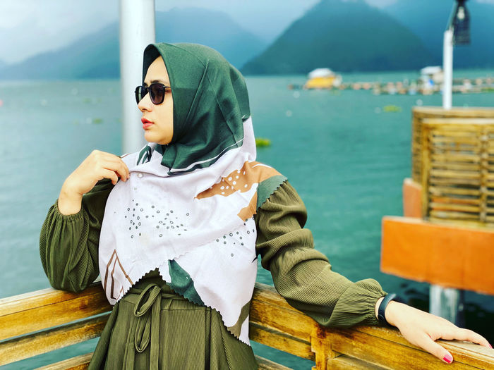 Young woman in scarf looking away against sea