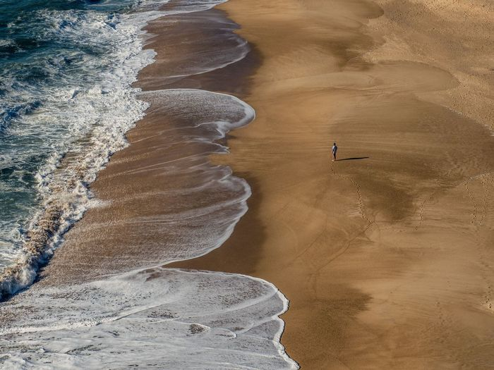 One man on the beach facing the waves on the shore of Nazaré Sand Beach Nature Sea Beauty In Nature Landscape Water Wave Outdoors No People Sand Dune Day Man One Person Holiday Travel Destinations Power In Nature Nazaré  Ocean One Man Only Portugal Lonely Been There. Lost In The Landscape Fresh On Market 2017 Go Higher