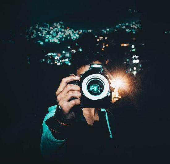 Man photographing through digital camera at night