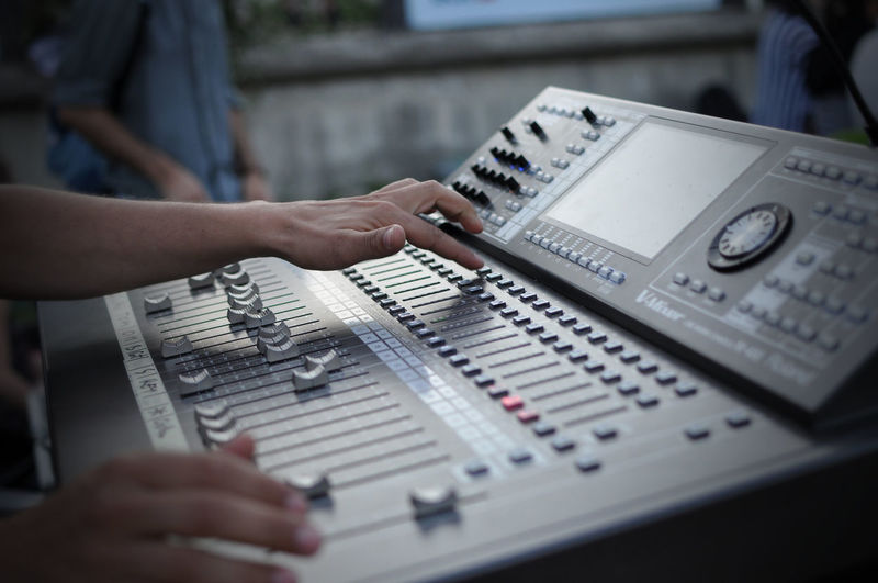 Cropped image of hand operating sound mixer