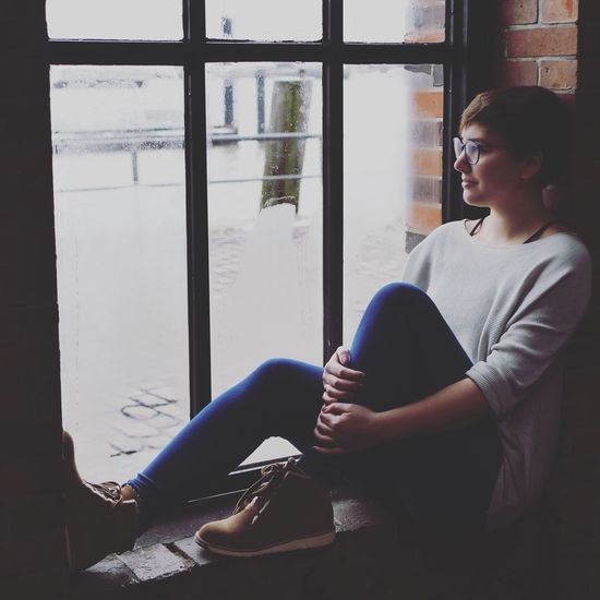 Woman sitting in window sill