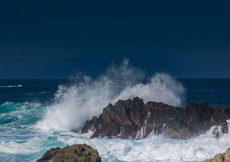 Waves splashing on rocks against clear sky