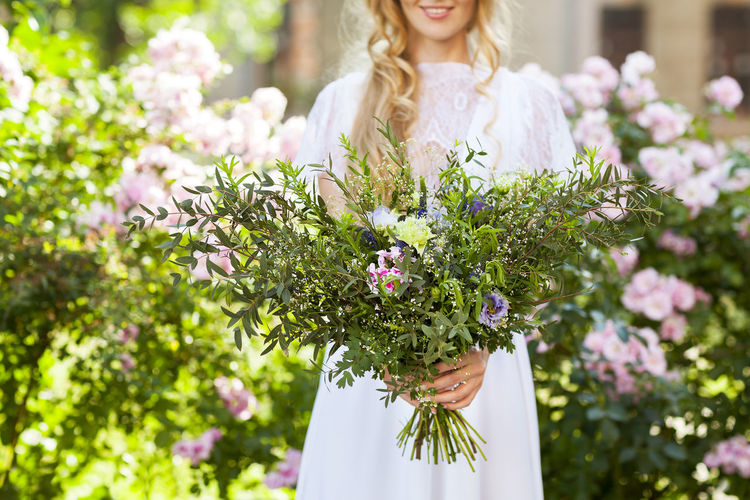 Low angle view of woman holding flowering plants