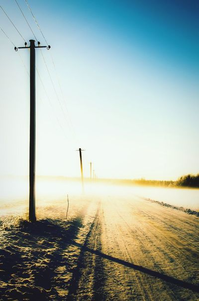 Dawn light on a foggy snowy road lined by telephone poles lost in a linear perspective Winter Snowy Snowfall Snow Road Morning Light Christmas Rural Countryside Remote Season  Snow Road Telephone Poles Cables Wires Fog Foggy Foggy Morning No People Estonia Landscape Linear Perspective Memory Lane Mist Blue Sky