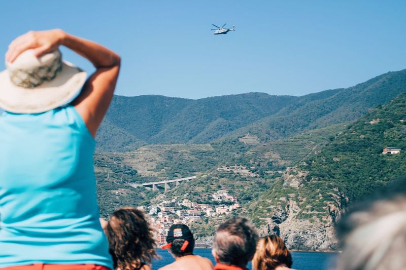 Rear view of people watching helicopter flying over mountain