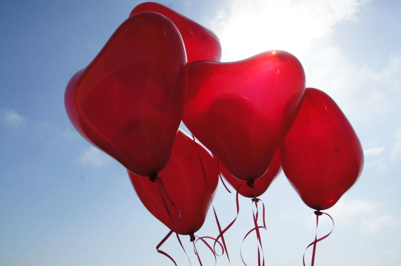 Low angle view of red love heart balloons against sky