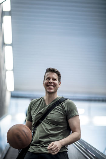 Low Angle View Of Young Man Playing With Basketball While Moving Down On Escalator