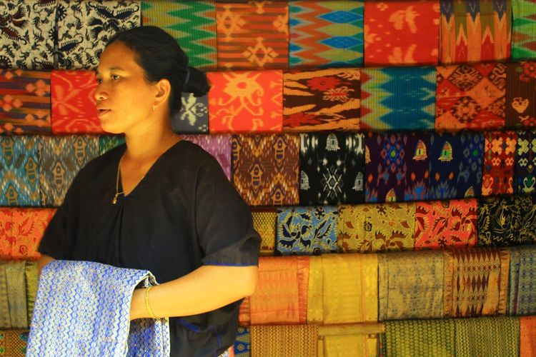 Woman looking away while standing against variety of textiles at market